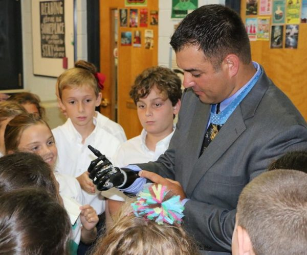 Medal of Honor Recipient Leroy Petry shares his artificial hand with students.
