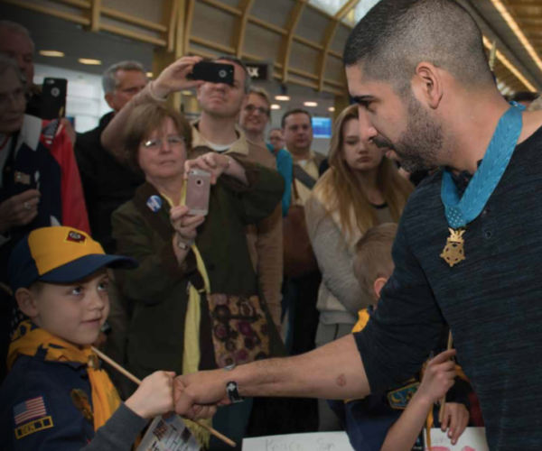 Medal of Honor Recipient Florent Groberg greets a young Scout.